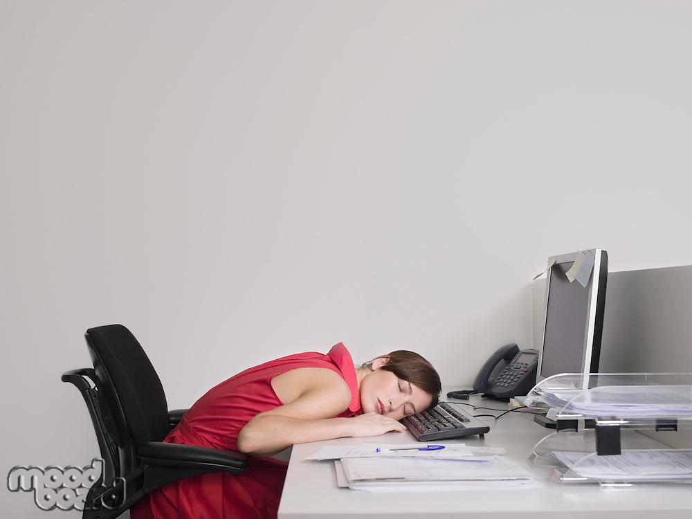 Female office worker asleep at desk in office