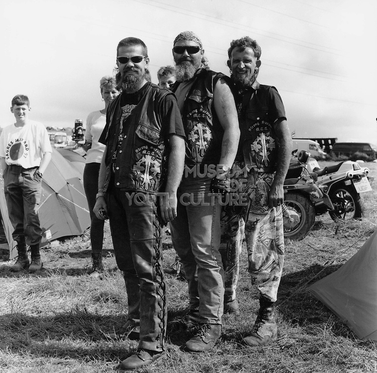 Three bearded bikers wearing leather waistcoats at a Rock and Blues festival