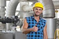 Portrait of confident young worker gesturing thumbs up in industry
