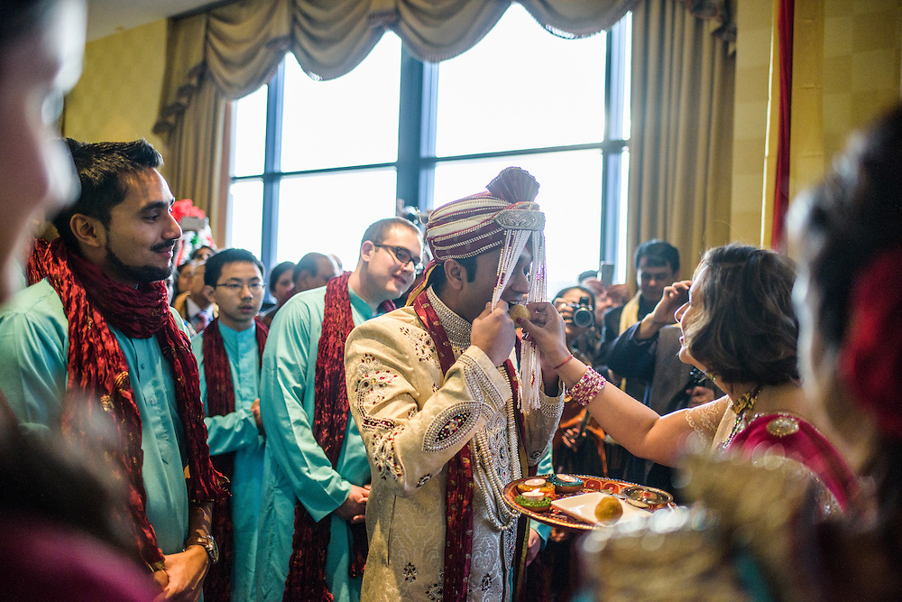Baltimore, Maryland - December 20, 2014: Mother of the bride Reena Pasricha perform the Dwar Puja, a traditional Indian welcome ritual, with her future son-in-law Eshwan Ramudu.<br /> Trisha Satya Pasricha and Eshwan Ramudu married at the Baltimore Marriott Waterfront Hotel December 20, 2014. <br /> <br /> <br /> CREDIT: Matt Roth for The New York Times<br /> Assignment ID: 30168620A