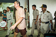"23 JANUARY 2013 - BANGKOK, THAILAND:  SOMYOT PRUESAKASEMUK walks into Bangkok Criminal Court followed by court security Wednesday. Somyot was sentenced to 11 years imprisonment Wednesday for violations of Thailand's ""Lese Majeste"" laws. He was arrested on April 30, 2011, and charged under article 112 of Thailand's penal code, which states that ""whoever defames, insults or threatens the King, the Queen, the Heir-apparent or the Regent, shall be punished with imprisonment of three to fifteen years"" after the magazine he edited, ""Red Power"" (later changed to ""The Voice of Thaksin"") published two articles by Jit Pollachan, the pseudonym of Jakrapob Penkair, the exiled former spokesman of exiled fugitive former Prime Minister Thaksin Shinawatra. Jakrapob, now living in Cambodia, has never been charged with any crime for what he wrote.      PHOTO BY JACK KURTZ"