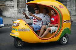 Coco Taxi carrying tourists in Havana,
