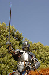 15th Century English knight in shining armour in a charge position on horseback