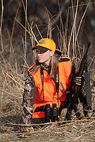 FEMALE HUNTER IN BLAZE ORANGE CARRYING A BLACK, AR-STYLE GUN