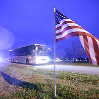 A pair of buses carrying members of the 155th HHC pass American flags that line the road leaving their facility in Tupelo Tuesday morning.