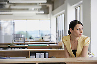 Pensive woman sitting at desk in office