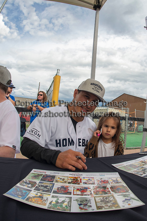 KELOWNA, CANADA - JUNE 28: Former NHL player Jordin Tootoo sings autographs for a young fan prior to the opening celebrity game of the Home Base Slo-Pitch Tournament fundraiser for Kelowna General Hospital Foundation's Jo-Ann's House on June 28, 2019 at Elk's Stadium in Kelowna, British Columbia, Canada.  (Photo by Marissa Baecker/Shoot the Breeze)