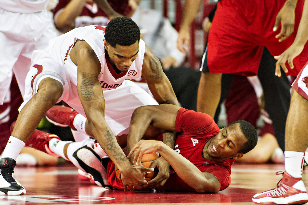 FAYETTEVILLE, AR - NOVEMBER 15:  Coty Clarke #4 of the Arkansas Razorbacks and Elridge Moore #22 of the Louisiana Ragin' Cajuns go to the floor after a ball at Bud Walton Arena on November 15, 2013 in Fayetteville, Arkansas.  The Razorbacks defeated the Ragin' Cajuns 76-63.  (Photo by Wesley Hitt/Getty Images) *** Local Caption *** Coty Clarke; Elridge Moore