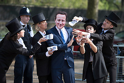 © Licensed to London News Pictures. 12/05/2016. London, UK. Police look on as a protestor dressed as Prime Minister David Cameron is offered fake money as he stands outside the anti-corruption summit. The real Mr Cameron is hosting a one day summit which is addressing world corruption. Photo credit: Peter Macdiarmid/LNP