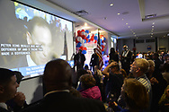 Garden City, New York, USA. November 6, 2018. Nassau County Democrats watch Election Day results at Garden City Hotel, Long Island. News broadcast shown on large screen has man discussing New York Congressional District 2 contest between Republican incumbent Congressman Pete King and Democratic challenger Liuba Grechen Shirley.