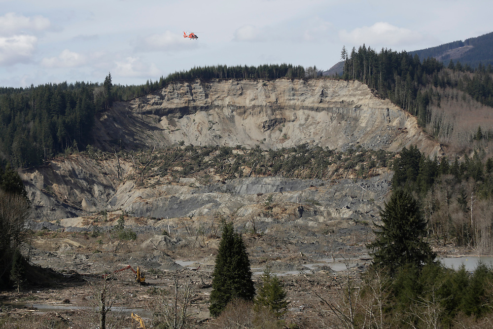 A U.S. Coast Guard helicopter flies over the area of a massive landslide that struck Oso, Washington as search work continues in the mud and debris below near Darrington, Washington March 31, 2014. Recovery teams struggling through thick mud up to their armpits and heavy downpours at the site of a devastating landslide in Washington state are facing yet another challenge - an unseen and potentially more dangerous stew of toxic contaminants. The official death toll was raised to 24 on Monday - up from 21 a day earlier - with 30 people still listed as unaccounted for nine days after a rain-soaked hillside collapsed above the north fork of the Stillaguamish River.  REUTERS/Jason Redmond (UNITED STATES)