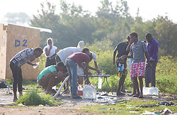 © Licensed to London News Pictures. 30/08/2015. Calais, France. People at the refugee camp in Calais, also known as the Jungle, get some water in the morning. Tomorrow the French PM, Manuel Valls, will visit the day centre Jules Ferry at the camp. Photo credit : Isabel Infantes/LNP