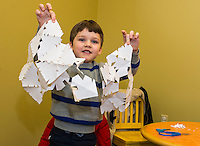"Luke Dorval-Drown shows off the snowflakes he made after reading ""Snowmen At Night"" during Laconia Library's preschool story hour on Wednesday morning.  (Karen Bobotas/for the Laconia Daily Sun)"