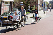 In Utrecht fietst een jongen met een meisje voorin de platte bakfiets door een fietsstraat waar auto's te gast zijn.<br /> <br /> In Utrecht a boy is cycling with a girl in a cargo bike.