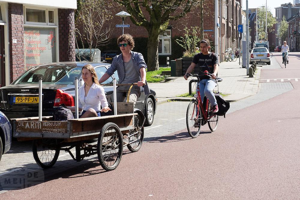 In Utrecht fietst een jongen met een meisje voorin de platte bakfiets door een fietsstraat waar auto's te gast zijn.<br /> <br /> In Utrecht a boy is cycling with a girl in a cargo bike.