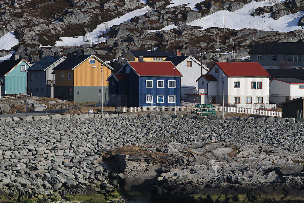 Colorful houses huddle between mountain and shore in the eastern Finnmark town of Kjollefjord, Norway.