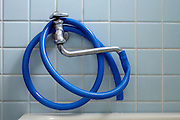 hose twisted around faucet in bathroom