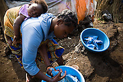 A woman carries her sleeping child on her back while washing blue berets belonging to MONUC peacekeepers in the CCLK (Centre Chrétien du Lac Kivu) spontaneous IDP site near Mugunga, on the outskirts of Goma, Eastern Democratic Republic of Congo on Wednesday December 17, 2008. Residents do such favors free of charge for MONUC troops, hoping for better protection. The site, that sprung up seven months ago, shelters over 2,500 people who have fled conflict.