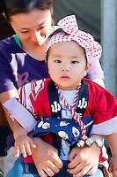 A young boy in traditional dress watches the parade of the Hokkaido Jingu Matsuri festival go past while sitting on his mother's knee.