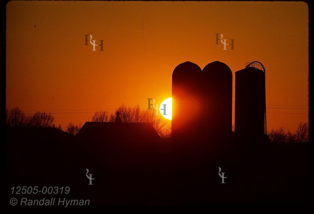 January sun sets behind silos on the Becker family farm near Laddonia. Missouri