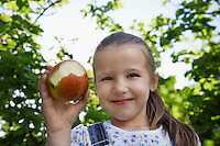 Girl (5-6) holding half-eaten apple outdoors portrait