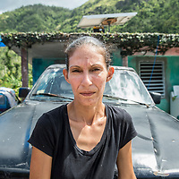 Sandra Colón Vardas in front of her house in Orocovis, Puerto Rico. It  is one of the very last households still without electricity, ten months after hurricane Maria. Sandra was given a small solar panel for the roof of her house by a support organization, that she can use to only run very basic appliances in her house of on, like lights in the evening and TV. Food is kept on ice in cooler boxes, the broken washing machine is sitting outside her house.