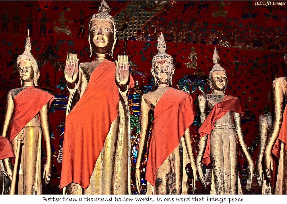 "Group of standing gilded wooden Buddha figures, each wrapped in a red stole, in a storeroom on the grounds of the Wat Xieng Thong in Luang Prabang, Laos.  One Figure in the foreground holds both hands in front in the ""peace"" gesture.  The others have their hands hanging down at their sides."