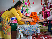 "04 APRIL 2015 - CHIANG MAI, CHIANG MAI, THAILAND: A woman sets up a boy's alter for the Poi Sang Long Festival at Wat Pa Pao in Chiang Mai. The Poi Sang Long Festival (also called Poy Sang Long) is an ordination ceremony for Tai (also and commonly called Shan, though they prefer Tai) boys in the Shan State of Myanmar (Burma) and in Shan communities in western Thailand. Most Tai boys go into the monastery as novice monks at some point between the ages of seven and fourteen. This year seven boys were ordained at the Poi Sang Long ceremony at Wat Pa Pao in Chiang Mai. Poy Song Long is Tai (Shan) for ""Festival of the Jewel (or Crystal) Sons.     PHOTO BY JACK KURTZ"