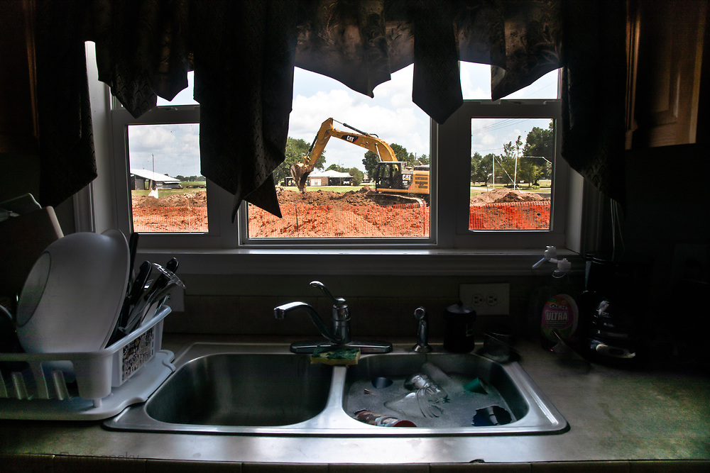 View of construction crew backfilling the trench burying the Bayou Bridge Pipeline, next to Melinda Tillies house in Youngsville, Louisiana from her kitchen. <br /> The pipeline was installed about 25 feet from her home on her neighbors land.  There are no federal rules about how close a pipeline can be built next to a home.