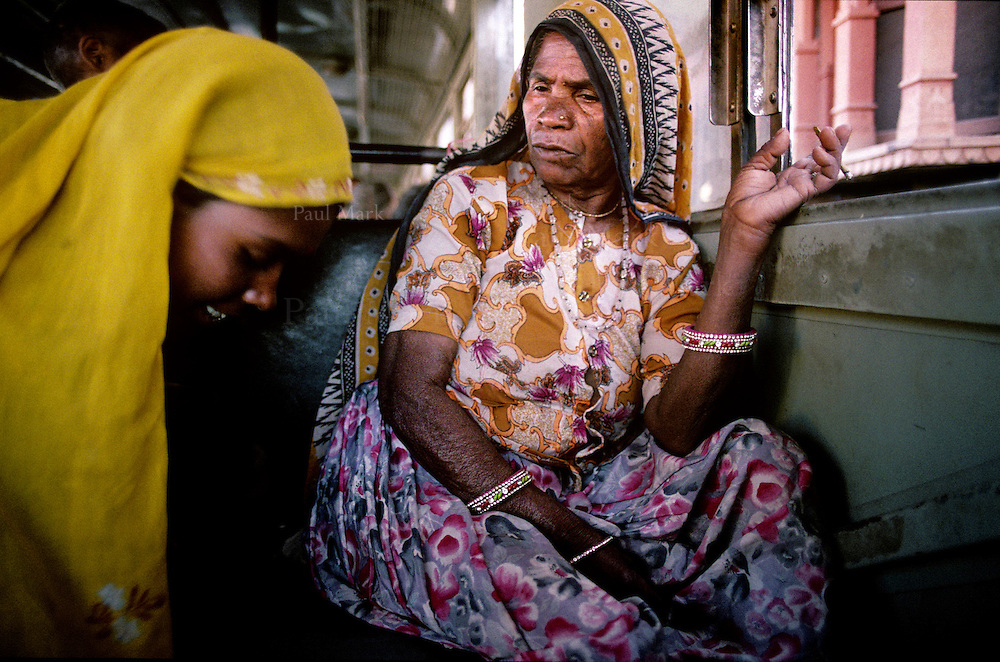 Rajasthani woman smoking a Beedi cigarette - an indian made cigarette of tabacco wrapped in a tendu leaf - on an inter-urban bus.