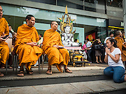 24 AUGUST 2015 - BANGKOK, THAILAND:  A woman prays at the feet of Buddhist monks presiding over a memorial service for victims of the Erawan Shrine bombing. One week after the a bomb at the Erawan Shrine in the center of Bangkok killed dozens and hospitalized scores of people, police have not made any arrests. Police bomb sniffing dogs have been deployed to malls and markets around Bangkok. There was a large memorial service sponsored by businesses close the bomb site Monday evening.     PHOTO BY JACK KURTZ