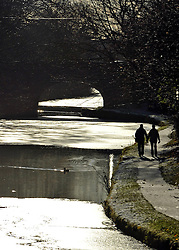 © Licensed to London News Pictures. 18/12/2011, London, UK.  Walkers on the tow path as the winter sun bounces of the ice on the canal. Canal boats in the frozen Leeds and Liverpool Canal, Central Lancashire, today 18 December. Photo credit : Stephen Simpson/LNP