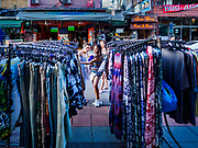 01 AUGUST 2018 - BANGKOK, THAILAND:     Tourists from Asia look at clothes at a street market stall on Khao San Road in Bangkok. Khao San Road is Bangkok's original backpacker district and is still a popular hub for travelers, with an active night market and many street food stalls. The Bangkok municipal government went through with it plans to reduce the impact of the street market on August 1 because city officials say the venders, who set up on sidewalks and public streets, pose a threat to public safety and could impede emergency vehicles. Venders are restricted to working from 6PM to midnight and fewer venders will be allowed to set up on the street. It's the latest in a series of night markets and street markets the city has closed.     PHOTO BY JACK KURTZ