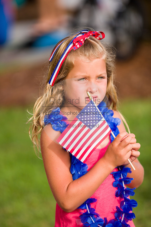 A young girl holds an American flag as she watches the Daniel Island Independence Day parade July 3, 2015 in Charleston, South Carolina.
