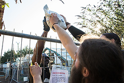 London, UK. 26th February, 2019. A bailiff from the National Eviction Team brings pet food to residents of Grow Heathrow. The squatted eco-community garden was founded in 2010 on a previously derelict site close to Heathrow airport in protest against government plans for a third runway and is since acknowledged to have made a significant educational and spiritual contribution to life in the Heathrow villages which are threatened by airport expansion. Bailiffs have evicted the protesters from the front section of the site, owned by Imran Malik, removing several protesters locked on in towers above the camp, but four protesters are believed to remain in a tunnel beneath that area. Many more protesters remain on the rear portion of the site. Five legal challenges to the government's approval of a 3rd runway at Heathrow will proceed to judicial review at the Royal Courts of Justice on 10th March.