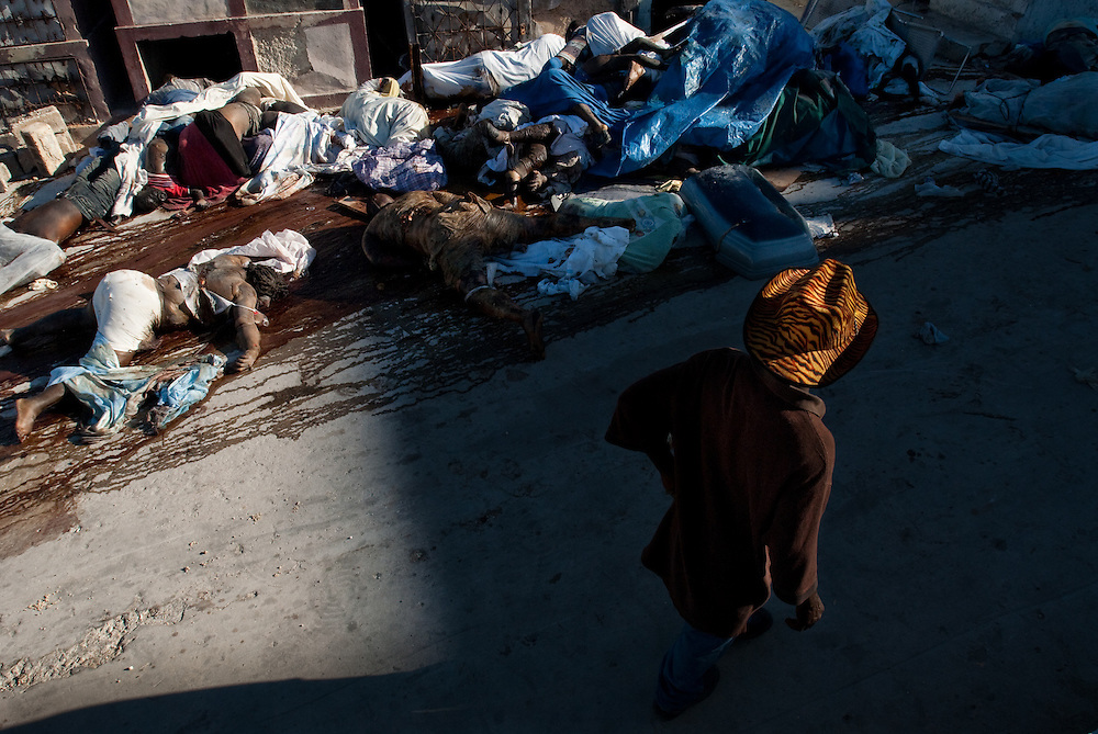 1/15/10 12:28:44 PM -- Port-Au-Prince, Haiti. -- Daily coverage of the aftermath of the 7.0 earthquake in Haiti -- A man walks past a stream of victim's of Tuesday's 7.0 magnitude earthquake that rocked the capital city of Port au Prince, Haiti, Friday Jan. 15, 2010. (Photo by William B. Plowman ©)