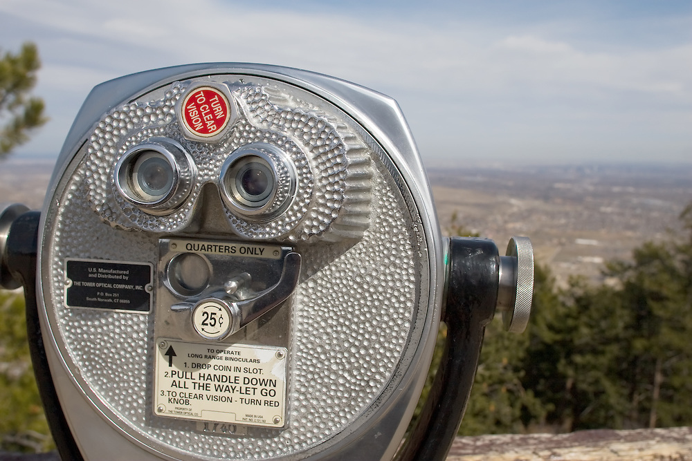A coin-operated tourist telescope on a scenic overlook in Golden, CO is used to view the skyline of Denver, CO, way in the distance.