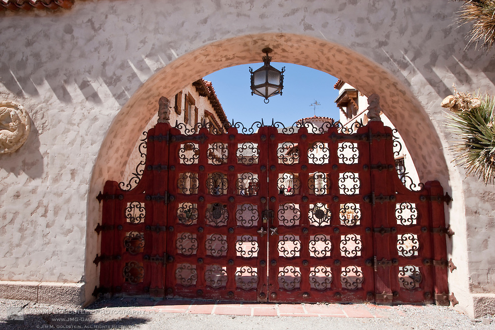 A tour group walks by on the others side of Scotty's Castle iconic gate - Death Valley National Park, California