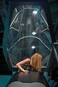 A lady visitor to the BAE Systems exhibition hall climbs out of a mock-up of the Tempest fighter, a replacement for the Typhoon, in the company's exhibition hall at the Farnborough Airshow, on 18th July 2018, in Farnborough, England.