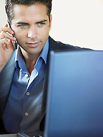 Businessman Using Cell Phone and Laptop Indoors