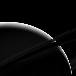 Although only a sliver of Saturn's sunlit face is visible in this view, the mighty gas giant planet still dominates the view. From this vantage point just beneath the ring plane, the dense B ring becomes dark and essentially opaque, letting almost no light pass through. But some light reflected by the planet passes through the less dense A ring, which appears above the B ring in this photo. The C ring, silhouetted just below the B ring, lets almost all of Saturn's reflected light pass right through it, as if it were barely there at all. The F ring appears as a bright arc in this image, which is visible against both the backdrop of Saturn and the dark sky. (For a diagram showing the names and positions of the rings see Expanse of Ice .)This view looks toward the unilluminated side of the rings from about 7 degrees below the ring plane. The image was taken in green light with the Cassini spacecraft wide-angle camera on Jan. 18, 2017.
