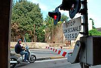 Le Ferrovie del Sud Est nascono in Puglia, nell'ottobre del 1931. A questà nuova società veniva dato in concessione l'insieme delle reti ferroviarie precedentemente gestite da diversi organismi (Società per le Ferrovie Salentine, Società per le Ferrovie Sussidiate, Ferrovie dello Stato)..Le aree pugliesi attraversate dalla società ferroviaria sono l'area barese, la fascia Taranto-Brindisi e l'area leccese-salentina, collegando fra loro i capoluoghi di Bari, Taranto e Lecce, nonché oltre 130 comuni delle province meridionali..Il reportage fotografico sulle Ferrovie Sud Est intende testimoniare l'evoluzione tecnologica che, durante gli anni, ha modificato e migliorato il servizio ferroviario e la convivenza del progresso con tracce del passato, attraverso un viaggio tra le stazioni e i depositi..Passaggio a livello della stazione di Bari Sud Est.