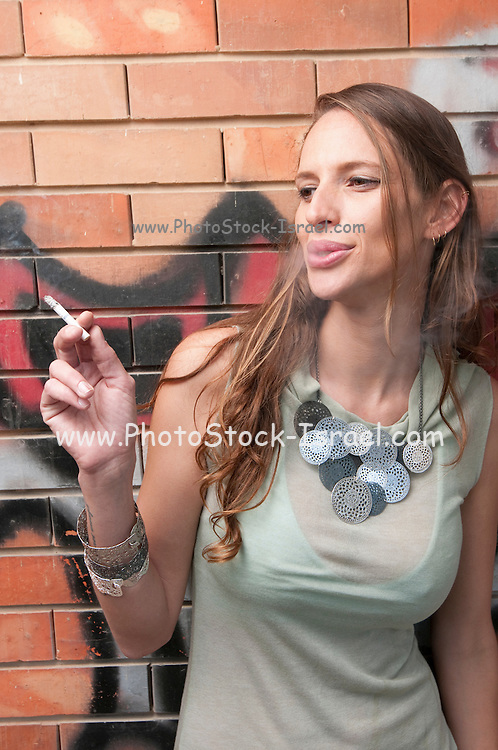 A hip and trendy young woman smoking in front of a brick wall with graffiti Model release available
