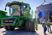 "06 AUGUST 2020 - FAIRFIELD, IOWA: A man climbs down from a combine being auction on the Adam Farm near Fairfield. Gary Adam, 72 years old, has been farming in the Fairfield area since 1971. He decided to retire this year because he wants to travel and because it's so difficult to make money in farming this year. He said he wants to ""shed the risk and responsibility. If things were super good, like they were 2006-2012, I might stay in it, but they're not."" An increasing number of farmers in the Midwest are retiring this year as it becomes harder to make money on crops. In addition to low prices, Iowa farmers are being hit with a drought this year, with well below average rain over most of the state. Because of the COVID-19 pandemic, the auction on Adam's farm was one of the first live in person auctions since winter. Most auctions are now done on line.    PHOTO BY JACK KURTZ"