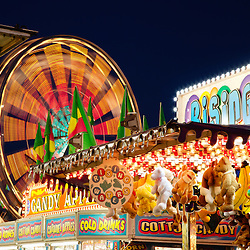 Picture of carnival games and Ferris Wheel at night spinning motion blurred. Photo is high resolution.