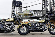 """A UH-1 """"Huey"""" helicopter lands behind two Harley-Davidson Softail Slim S motorcycles to escort veterans to America's Parade in New York on Veterans Day, Wednesday, Nov. 11, 2015, in Kearny, NJ.  Harley-Davidson announced the extension of """"Operation Personal Freedom: Ride Free,"""" free Riding Academy motorcycle training to all active-duty military and veterans. (Photo by Diane Bondareff/AP Images for Harley-Davidson)"""