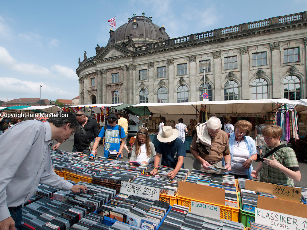 People browsing second hand movies at outdoor weekend flea market beside Museumsinsel with Bode Museum to rear  in Mitte Berlin Germany