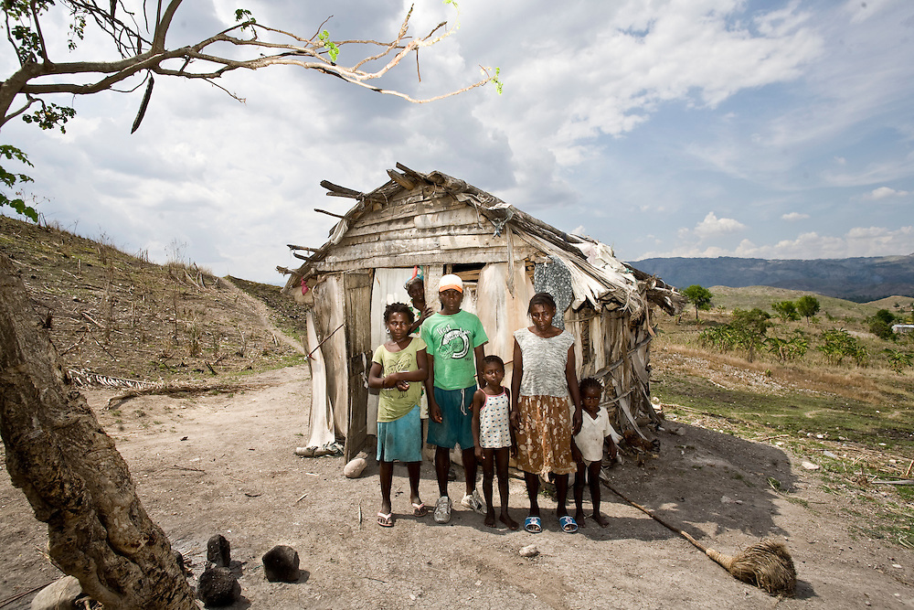 A family poses for a picture in front of their home.