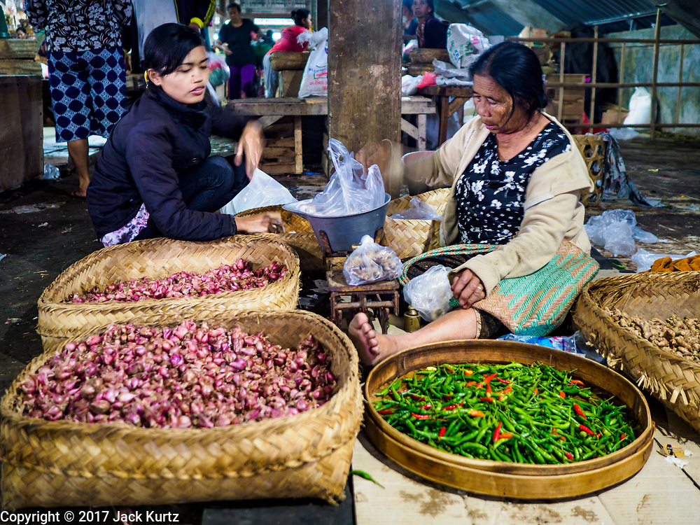 04 AUGUST 2017 - PAYANGAN, BALI, INDONESIA: A woman sells garlic and chillies in the local market in Payangan, about 45 minutes from Ubud. Bali's local markets are open on an every three day rotating schedule because venders travel from town to town. Before modern refrigeration and convenience stores became common place on Bali, markets were thriving community gatherings. Fewer people shop at markets now as more and more consumers go to convenience stores and more families have refrigerators.      PHOTO BY JACK KURTZ