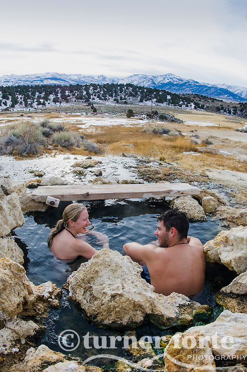 Couple soaks in winter at Travertine Hot Springs, Eastern Sierras, California.
